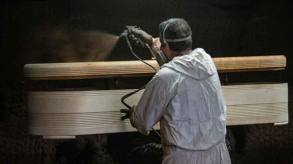 Un operario durante el proceso de lacado de uno de los féretros.