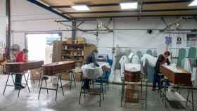 Varios empleados durante la última fase de producción de los ataúdes antes de su comercialización.