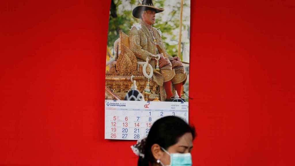 Una ciudana de Tailandia, en una calle de Bangkok, con el retrato del rey al fondo.