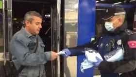 Un policía municipal reparte mascarillas este lunes en el Metro de Madrid.