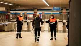 El personal de seguridad reparte mascarillas a la entrada de la estación de Atocha Renfe.