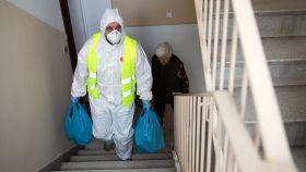 Un voluntario ayuda a una anciana a subir las bolsas de la compra, en Atenas.