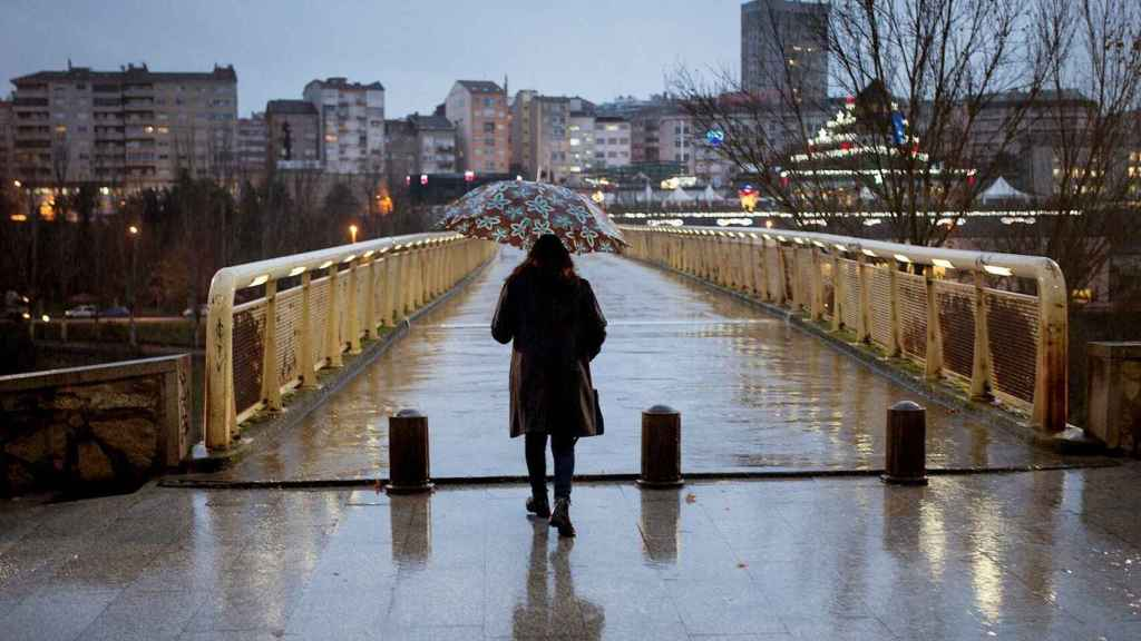 Una imagen de archivo de una mujer mientras pasea por las calles de Orense.