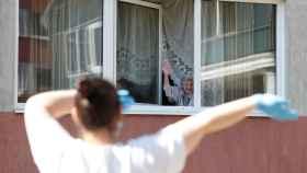 Una anciana se asoma a la ventana de la residencia en la que vive para disfrutar de la música que suena en la calle.