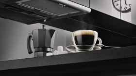 Una cafetera italiana junto a una taza de café solo.