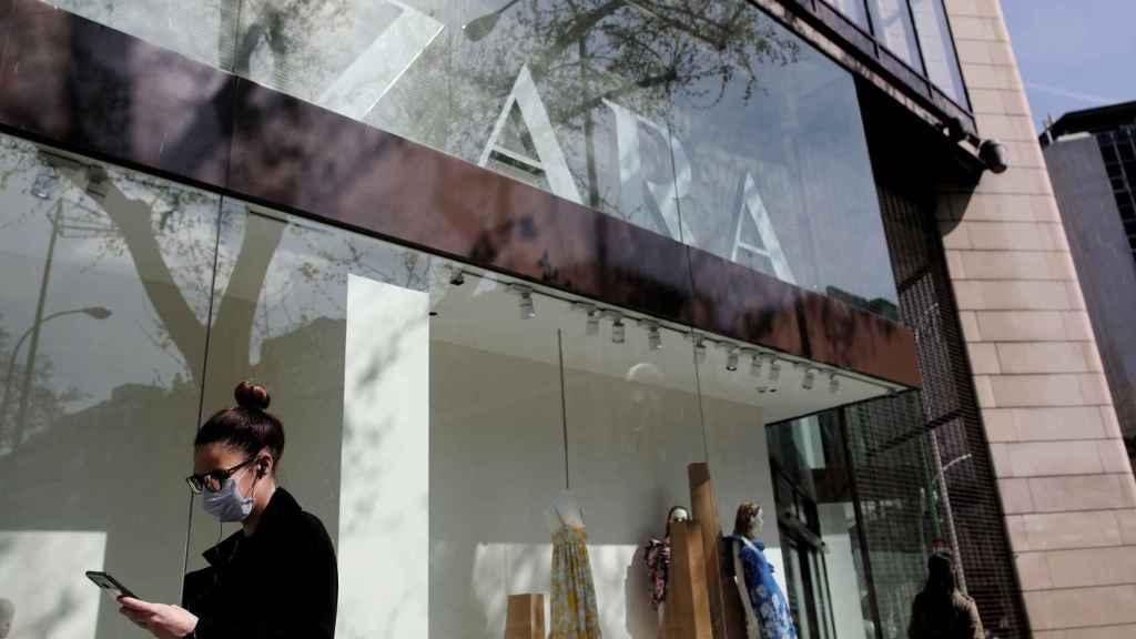 Una mujer con mascarilla pasa junto al escaparate de la tienda Zara de la Calle Princesa de Madrid del grupo Inditex.