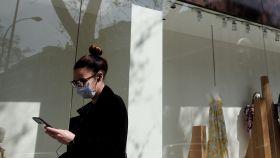 Una mujer con mascarilla maneja un móvil frente a una tienda.