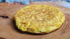 Una tortilla de patata redonda y dorada.