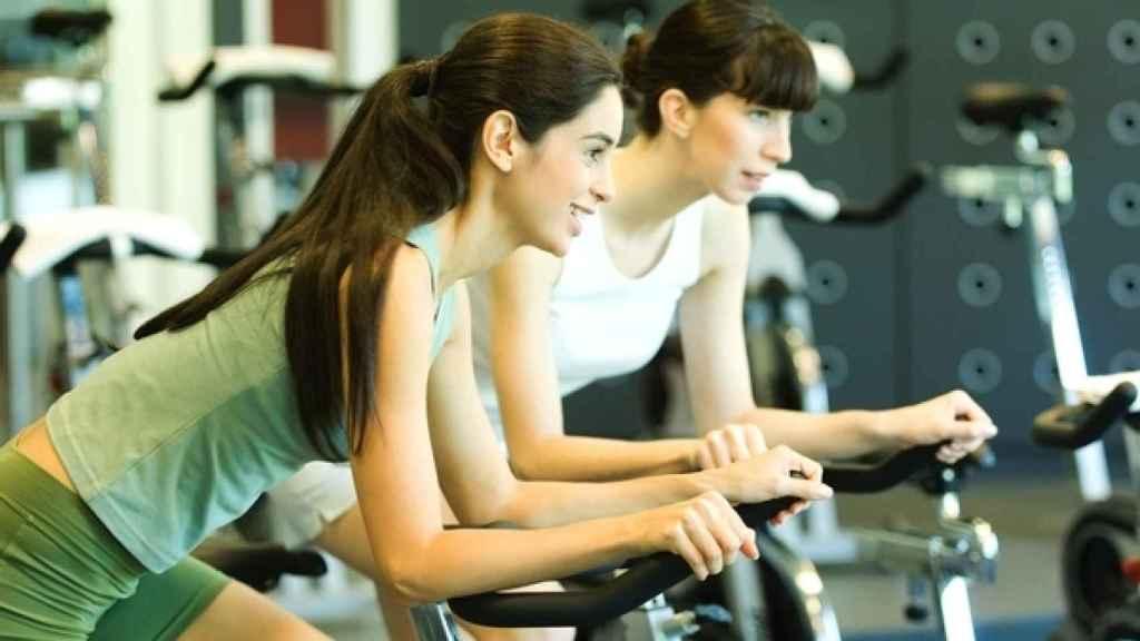 Dos mujeres hacen ejercicio en bicicletas estáticas.