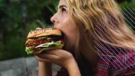 Una mujer comiendo una hamburguesa.