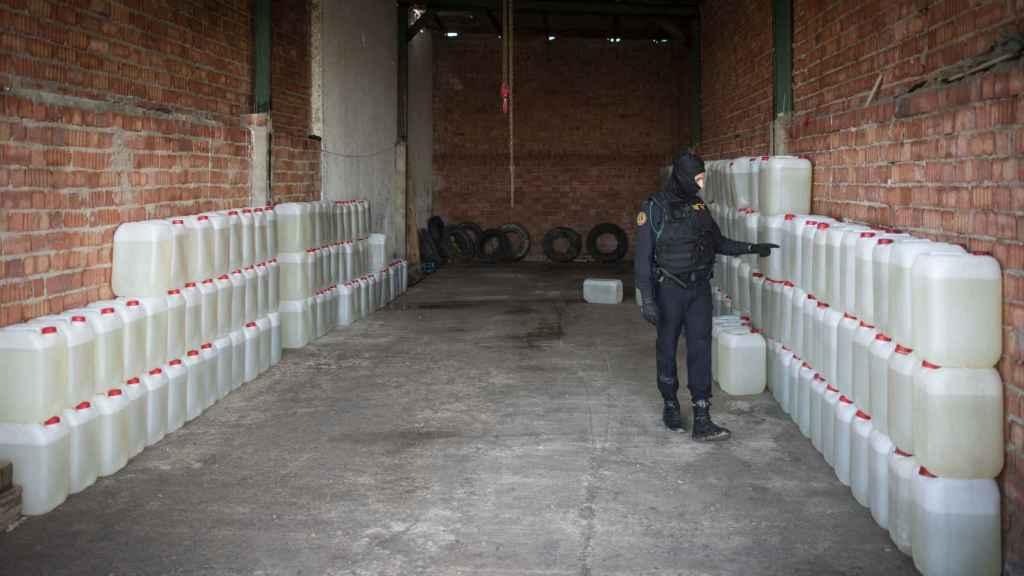 Un agente de la Guardia Civil cuenta el número de bidones de gasolina incautados en una nave de Lebrija (Sevilla).
