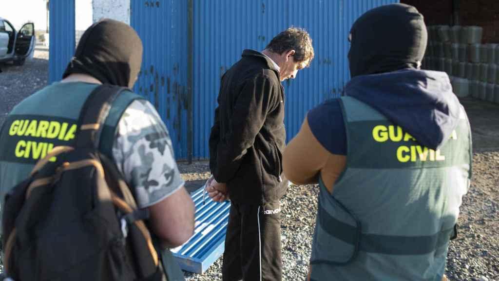 El detenido en Lebrija, custodiado por dos agentes de la Guardia Civil.
