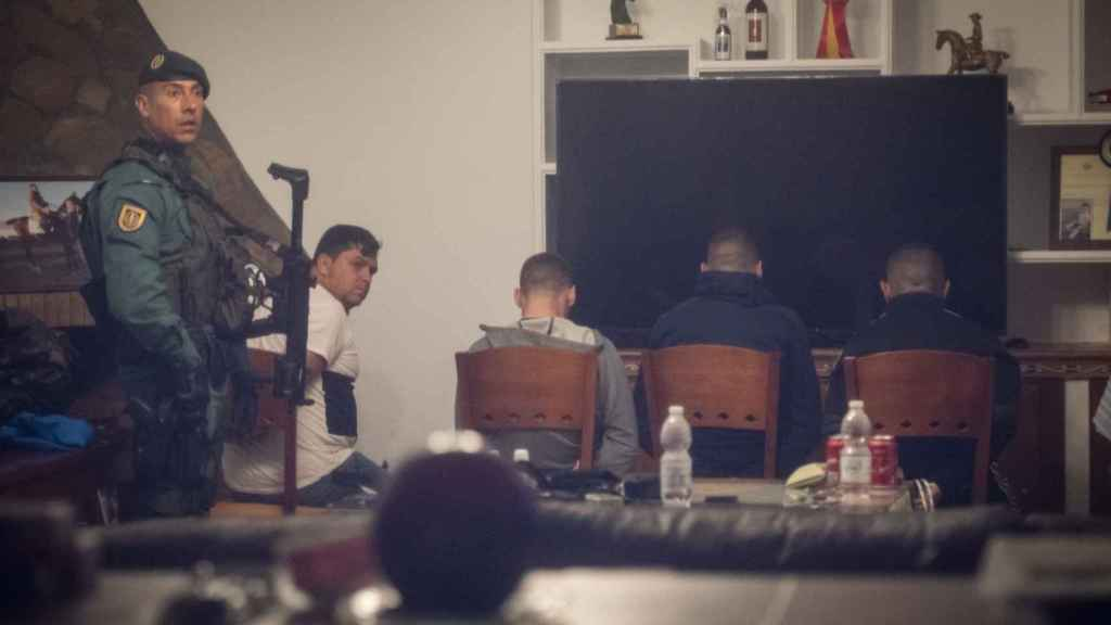 Los cuatro detenidos en un chalet de Trebujena (Cádiz), custodiados por un guardia civil.