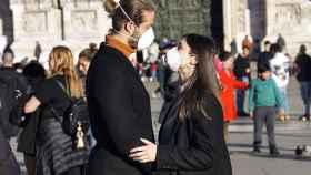 Dos jóvenes en Italia con una mascarilla protectora.