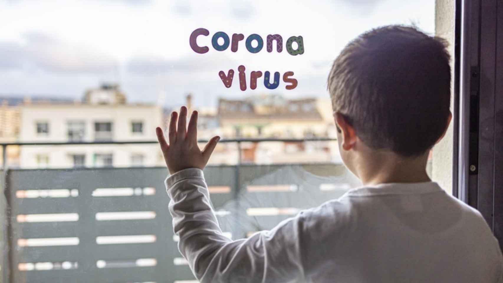 Un niño mira por la ventana mientras se encuentra confinado en su casa.