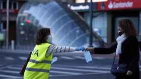 Una voluntaria de la DYA realiza una entrega de mascarilla a una mujer en la capital vizcaína.