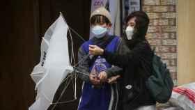 Dos mujeres luchan contra el viento en Corea del Sur.