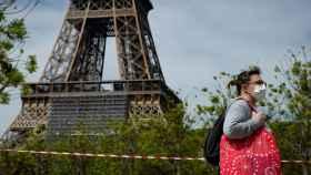 Una mujer camina con mascarilla cerca de la torre Eiffel