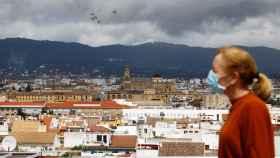 Una mujer camina este martes con el fondo de la Mezquita-Catedral de Córdoba y un cielo cubierto de nubes oscuras.