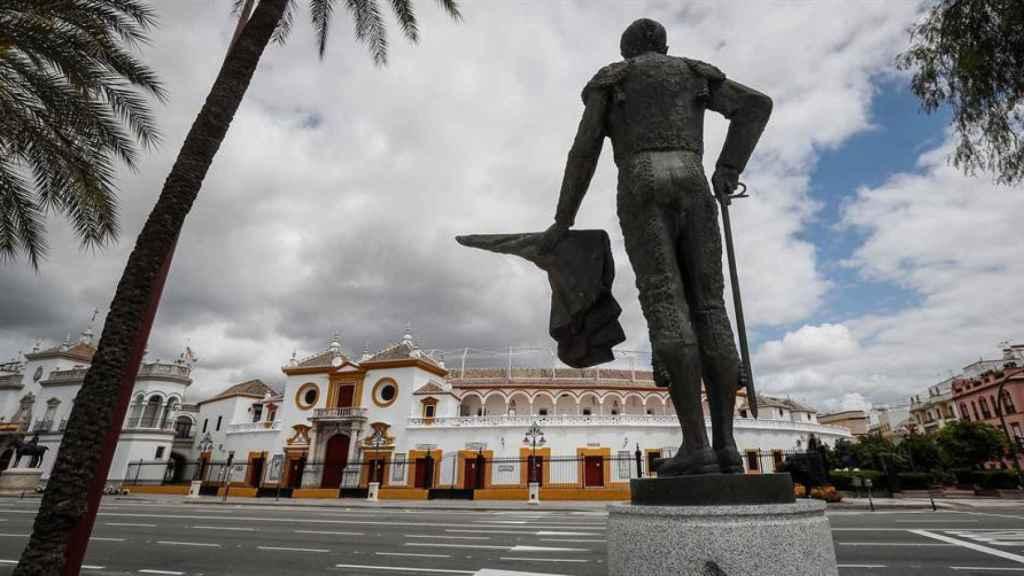 Plaza de toros de la Real Maestranza de Sevilla desde la escultura del diestro Pepe Luis Vázquez en un Paseo de Colón vacío.