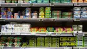 Una estantería de supermercado con conservas de pescado.