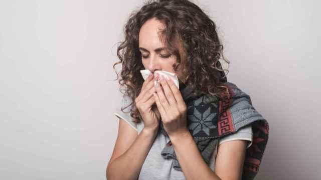 Una joven se lleva un pañuelo a la boca.