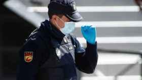Un agente con el rostro cubierto con una mascarilla.
