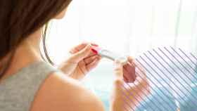 Una mujer mirando un test de embarazo.