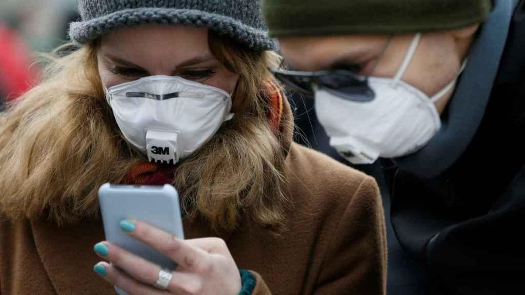 Personas con mascarillas usando el smartphone.