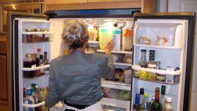 Una mujer mete alimentos en la nevera.