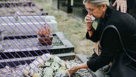 Una mujer dejando flores en una tumba.