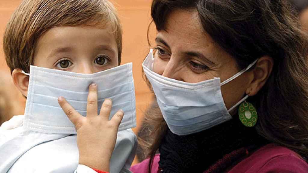 Un niño acude al coelgio con mascarilla, acompañado de su madre.