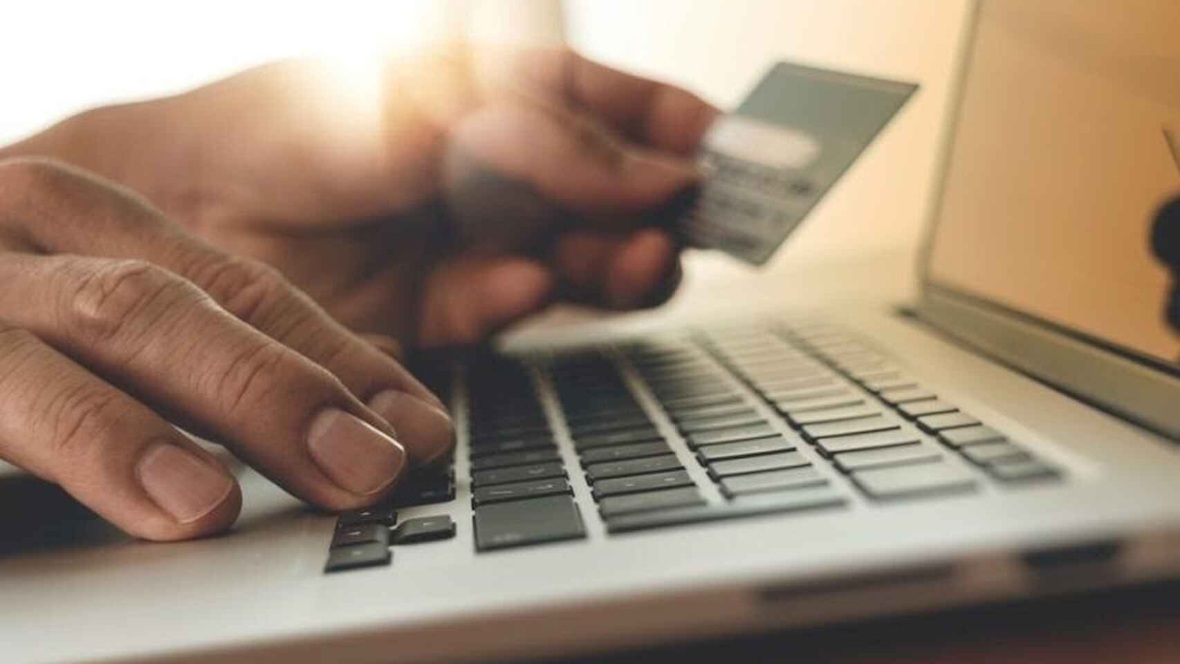 Una persona usando un ordenador con tarjeta de crédito y haciendo compras online.
