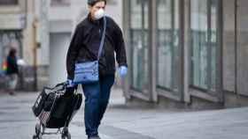 Una mujer con mascarilla, guantes y un carro de la compra.