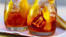 Dos vasos de vermú rojo servido con hielo y piel de limón.