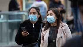 Dos mujeres andan por la calle con mascarillas en la cara.