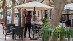 Un camarero prepara la terraza de un bar.