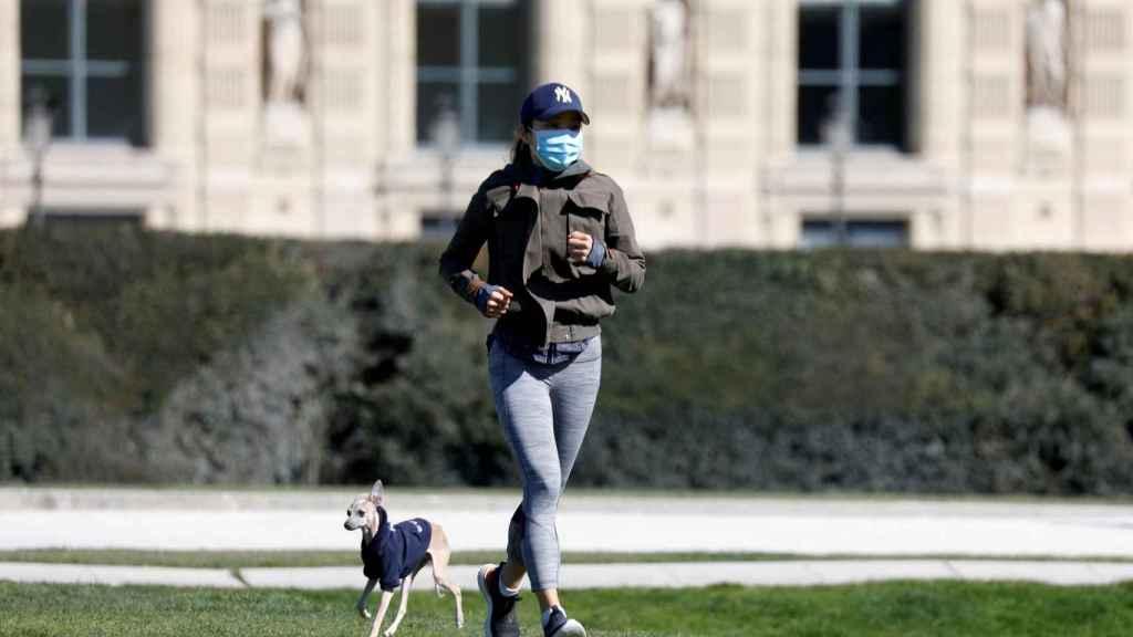 Una mujer corriendo con mascarilla.