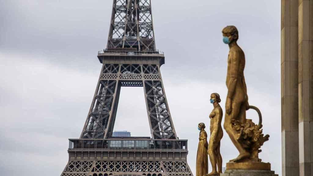 Las estatuas doradas de la Plaza de Trocadero en París, adornadas con mascarillas.