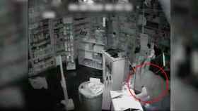 Uno de los ladrones, asaltando la caja registradora de una farmacia.