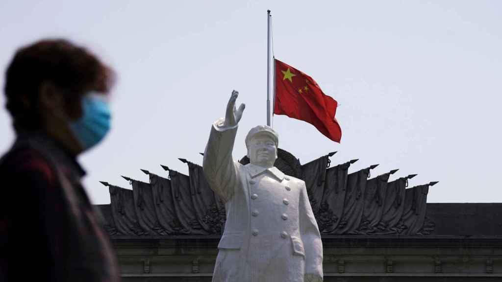 Una mujer con mascarilla pasa delante de una estatua de  Mao Zedong en Wuhan.
