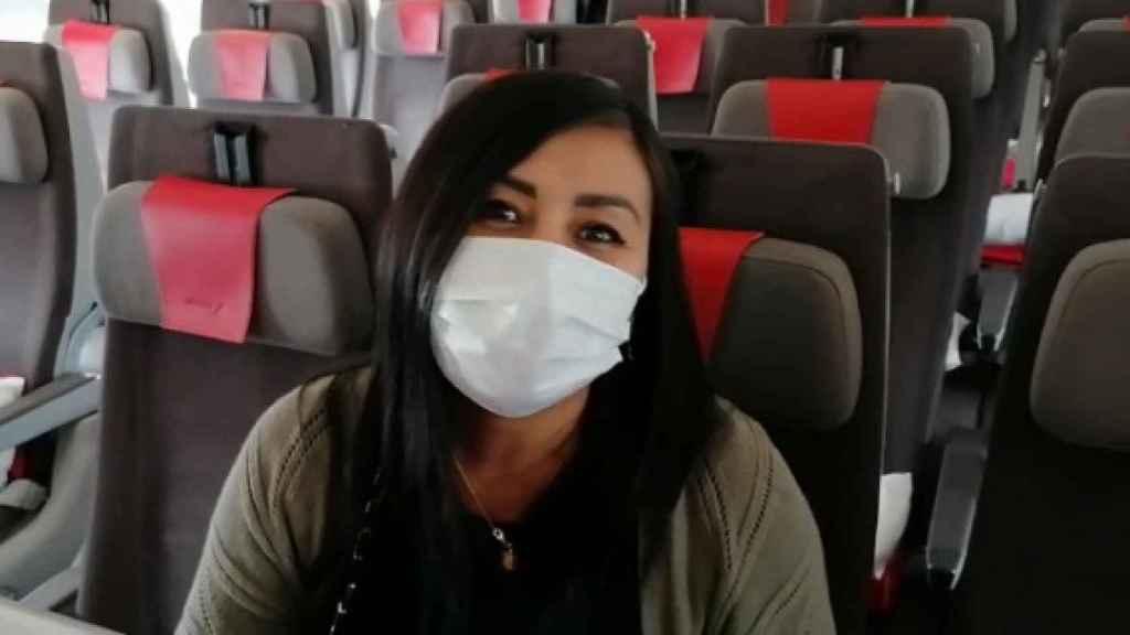 Una pasajera con mascarilla a bordo de un avión.