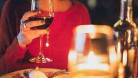 Una mujer cena con un vino tinto.