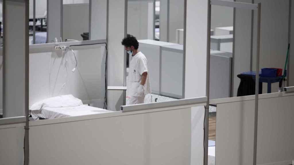 : Un profesional sanitario frente a una cama vacía en el hospital de campaña de IFEMA. Eduardo Parra / Europa Press
