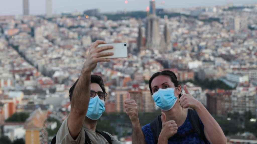 Una pareja se hace un 'selfie' con mascarilla en Barcelona.