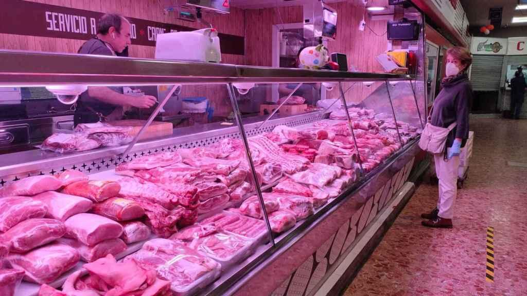 Una clienta espera su turno en una carnicería de Madrid.