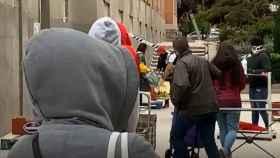Largas colas para obtener una bolsa de comida en Madrid.