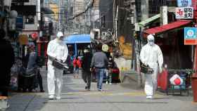 Un operario desinfecta una calle del barrio de Itaewon, en Seúl.