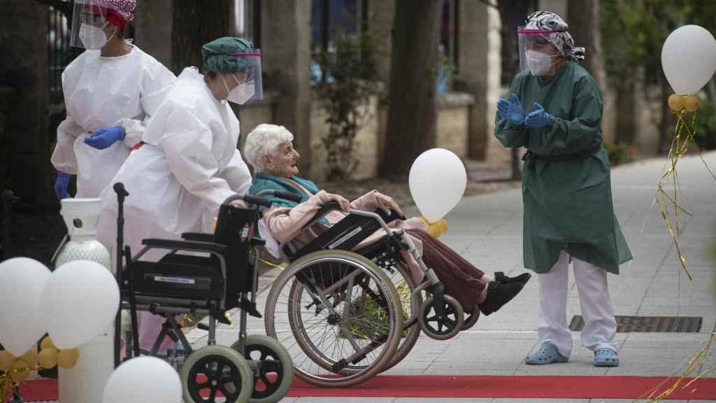 Una anciana en silla de ruedas conducida por personal sanitario a su llegada a la residencia La Pasionaria.