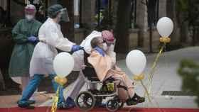 Una anciana en silla de ruedas recibe el cariño del personal sanitario a su llegada a la residencia La Pasionaria.